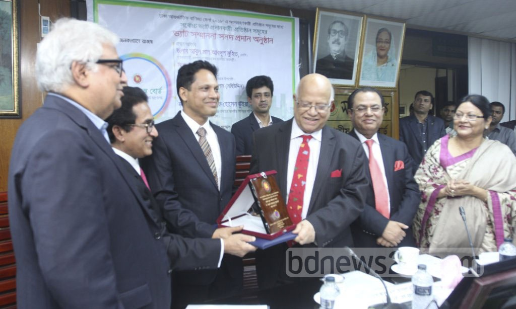 Finance Minister AMA Muhith hands awards to highest VAT payers among participators of the Dhaka International Trade Fair during ceremony at the National Board of Revenue offices on Monday. Photo: Abdullah Al Momin