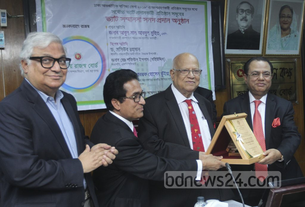 Finance Minister AMA Muhith hands the best tax payer award to former minister Syed Abul Hossain on Monday during a ceremony at the National Board of Revenue offices. Photo: Abdullah Al Momin