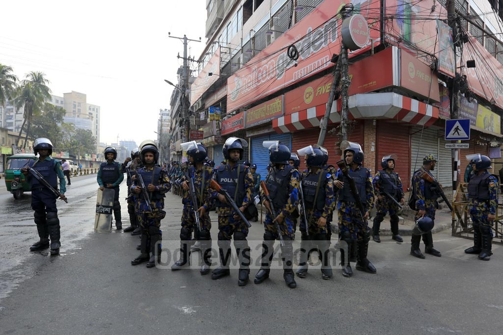 A contingent of armed-police battalion men guarding the deserted road at Bakshaibazar area on Thursday as the capital comes under a security blanket over the verdict of Zia Orphanage Trust graft case against BNP chief Khaleda Zia. Photo: mostafigur rahman