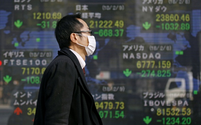 A man walks past an electronic board showing the stock market indices of various countries outside a brokerage in Tokyo, Japan Feb 9, 2018. Reuters