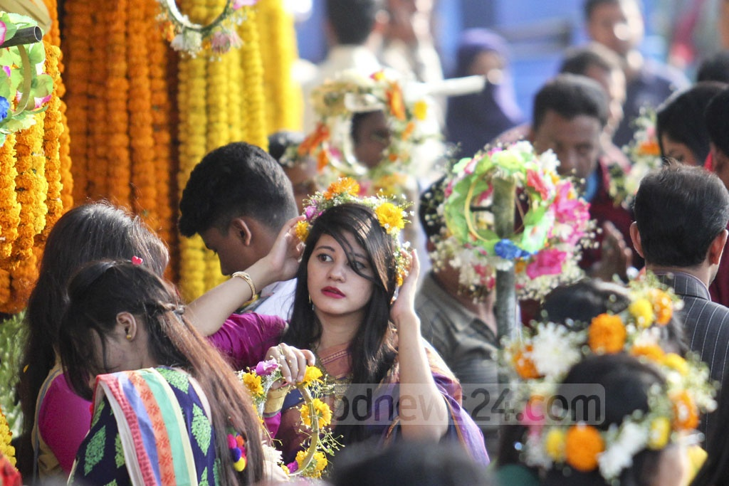 A young girl gets her head decorated with a flower ring to add more colour to the celebrations on the first day of the Falgun, the first Bengali month of the spring season or Basanta, at Shahbagh on Tuesday. Photo: asif mahmud ove