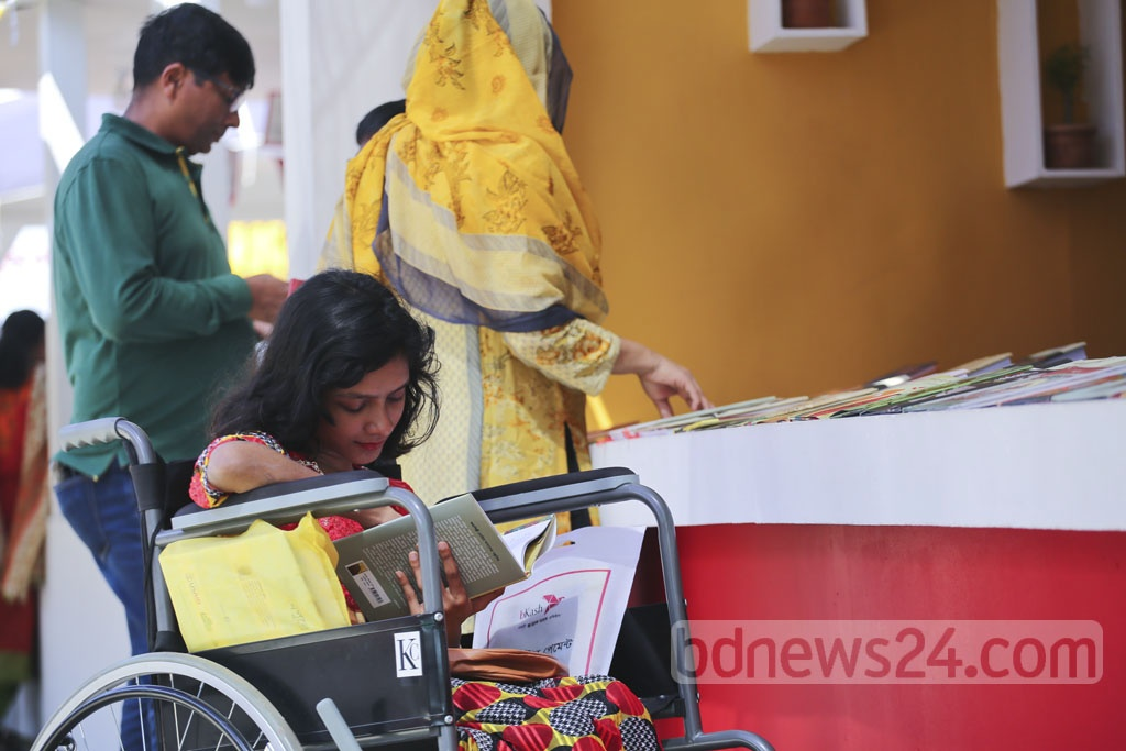 Her physical disability could barely hold 'Moutusi' back as she visits the Amar Ekushey Book Fair on a wheelchair on Friday. Photo: Mahmud Zaman Ovi