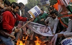 Activists of the youth wing of India's main opposition Congress party burn banners with an image of billionaire jeweller Nirav Modi during a protest in New Delhi, India February 16, 2018. Reuters