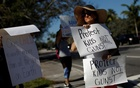 People holding placards take part in a protest in support of the gun control at a street corner in Coral Springs, Florida, US, Feb 17, 2018. Reuters