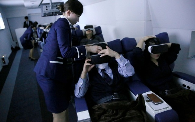Staff dressed as flight attendants, help guests to wear virtual reality (VR) goggles at the