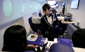 A staff dressed as flight attendant, serves appetizers to guests at the