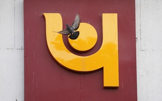 A pigeon flies past the logo of Punjab National Bank outside a branch of the bank in New Delhi, India Feb 15, 2018. Reuters