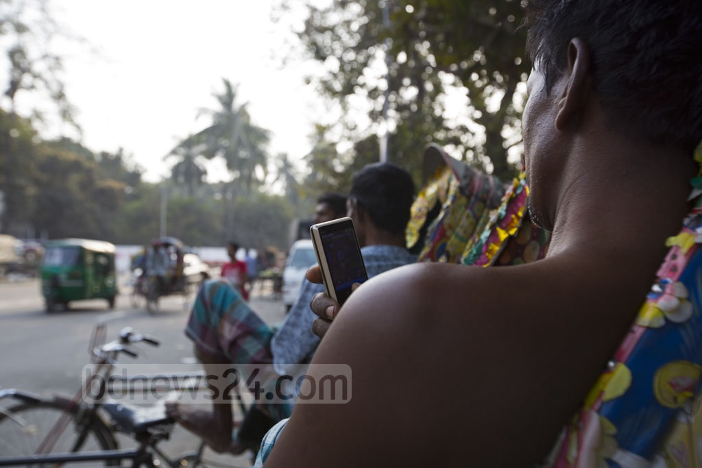 A rickshaw-puller watching video clips on his mobile phone as he takes a break. Photo taken on Tuesday near the Central Shaheed Minar in Dhaka. Photo: mostafigur rahman