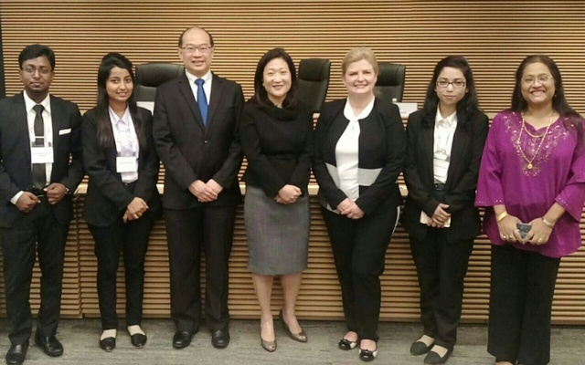 The members of the East West University moot team pose for a photo with the judges of the competition.