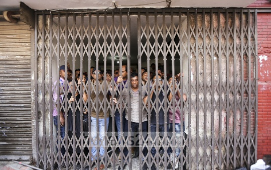 BNP activists chant slogans after retreating inside the party's headquarters in Naya Paltan following a police baton charge.