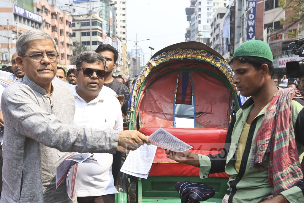 BNP Secretary General Mirza Fakhrul Islam Alamgir hands out leaflets to a rickshaw-puller at Dhaka's Naya Paltan on Thursday, calling for the release of party Chairperson Khaleda Zia from jail. Photo: Abdullah Al Momin