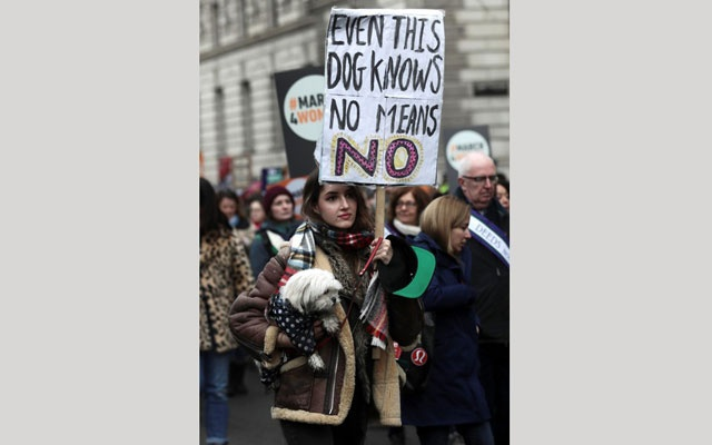 A protestor holds her dog alongside a placard as she demonstrates during the March4Women event in central London, Britain March 4, 2018. REUTERS