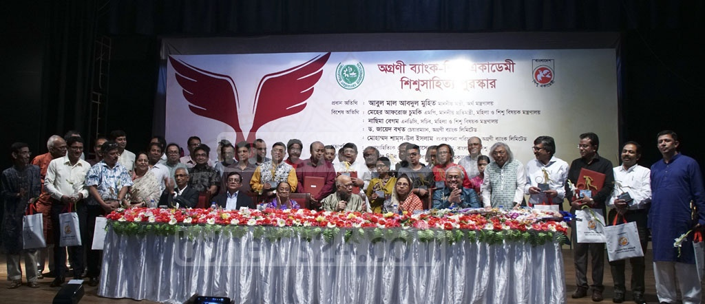 The winners of Agrani Bank Shishu Academy Children's Literature Awards pose for a group photo with the guests at the awards ceremony at Shishu Academy Auditorium in Dhaka on Saturday. As many many 39 writers who won the awards in six years from 1418 to 1423 of the Bangla calendar received the awards at the programme. Photo: Mahmud Zaman Ovi