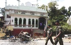 Sri Lanka's Special Task Force soldiers walk past a damaged mosque after a clash between two communities in Digana central district of Kandy, Sri Lanka March 8, 2018. Reuters