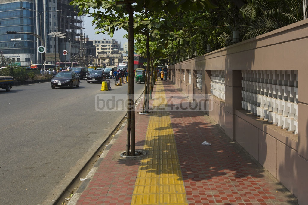 The visually impaired people can easily identify the raised strip of tiles on the pavement with their feet and measure their position while walking along the footpath or crossing the road. A section of capital's Kazi Nazrul Islam Avenue is fitted with the new tiles. The photo is taken on Tuesday. Photo: mostafigur rahman