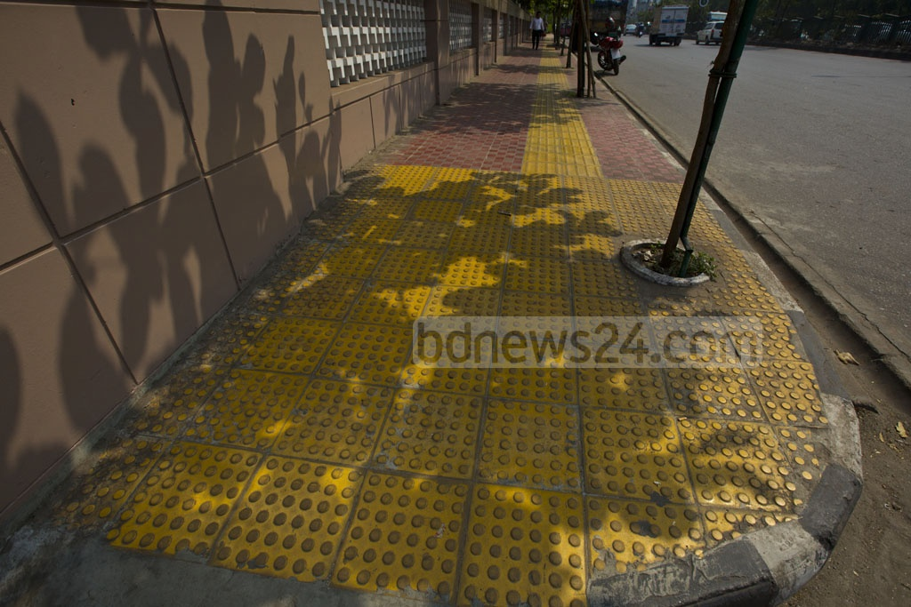 The visually impaired people can easily identify the raised strip of tiles on the pavement and measure their position while walking along the footpath or crossing the road. A section of Kazi Nazrul Islam Avenue is fitted with the new tiles. The photo is taken on Tuesday. Photo: mostafigur rahman