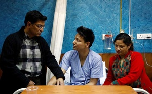 Sanam Shakya, 33, a survivor from the US-Bangla plane crash speaks with his father as his mother sits next to him while undergoing treatment at a hospital in Kathmandu, Nepal March 12, 2018. Reuters