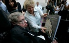 British physicist Stephen Hawking looks at a book of Chile's Nobel Laureate Pablo Neruda after a meeting with Chile's President Michelle Bachelet (unseen) at the Presidential Palace in Santiago Jan 17, 2008. Reuters