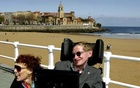 British astrophysicist Stephen Hawking (R) and his wife Elaine pose in front of the San Lorenzo beach in the northern Spanish city of Gijon Apr 10, 2005. Reuters