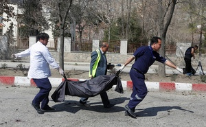 Afghan officials carry a body of a victim at the site of a suicide bomb attack in Kabul, Afghanistan Mar 21, 2018. Reuters
