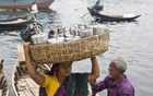 They are called Bangladeshi 'dabbawalas', crossing Buriganga everyday from Jinjira with lunch boxes from Jinjira to different shops in Chawkbazar, the old part of Dhaka. The woman in picture has been doing it for the last 10 years and earns Tk 250 to Tk 350 for each tiffin box a month. Photo: mostafigur rahman