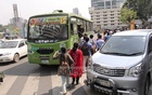 Passengers scramble to get on to a bus as it slowed down in the middle of the road while other vehicles are passing by. The picture is taken from Karwan Bazar on Thursday. Photo: asif mahmud ove