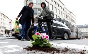 Brussels resident Anton Schuurmans talks to a cyclist after planting flowers in an unrepaired pothole to draw attention to the bad state of public roads in Brussels, Belgium April 5, 2018. Reuters