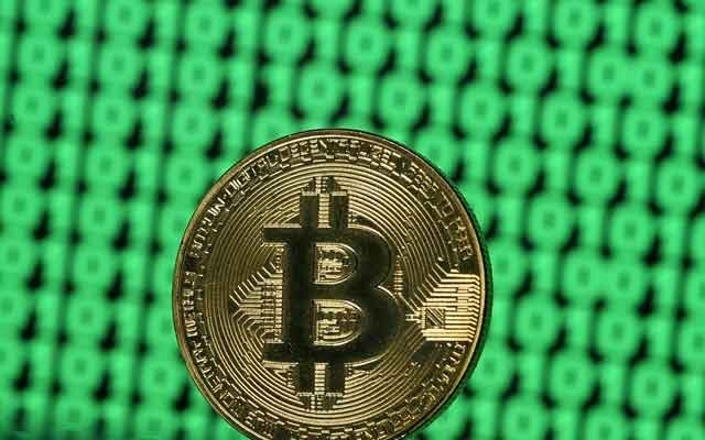 A token of the virtual currency Bitcoin is seen placed on a monitor that displays binary digits in this illustration picture, Dec 8, 2017. Reuters
