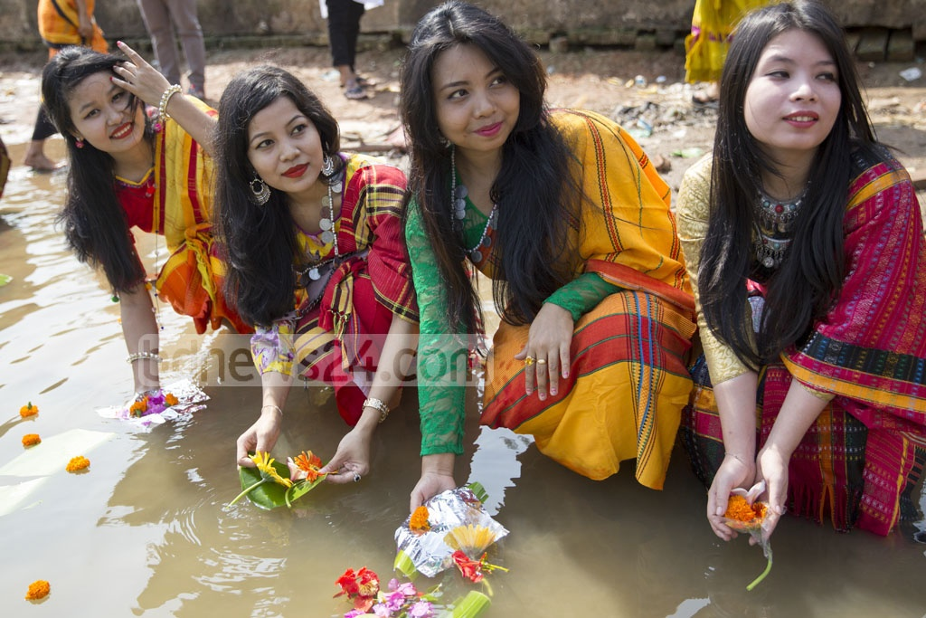 Members of minority ethnic groups place flowers at the Dhaka's Crescent Lake on Thursday to celebrate Baishabi. Photo: Mostafigur Rahman