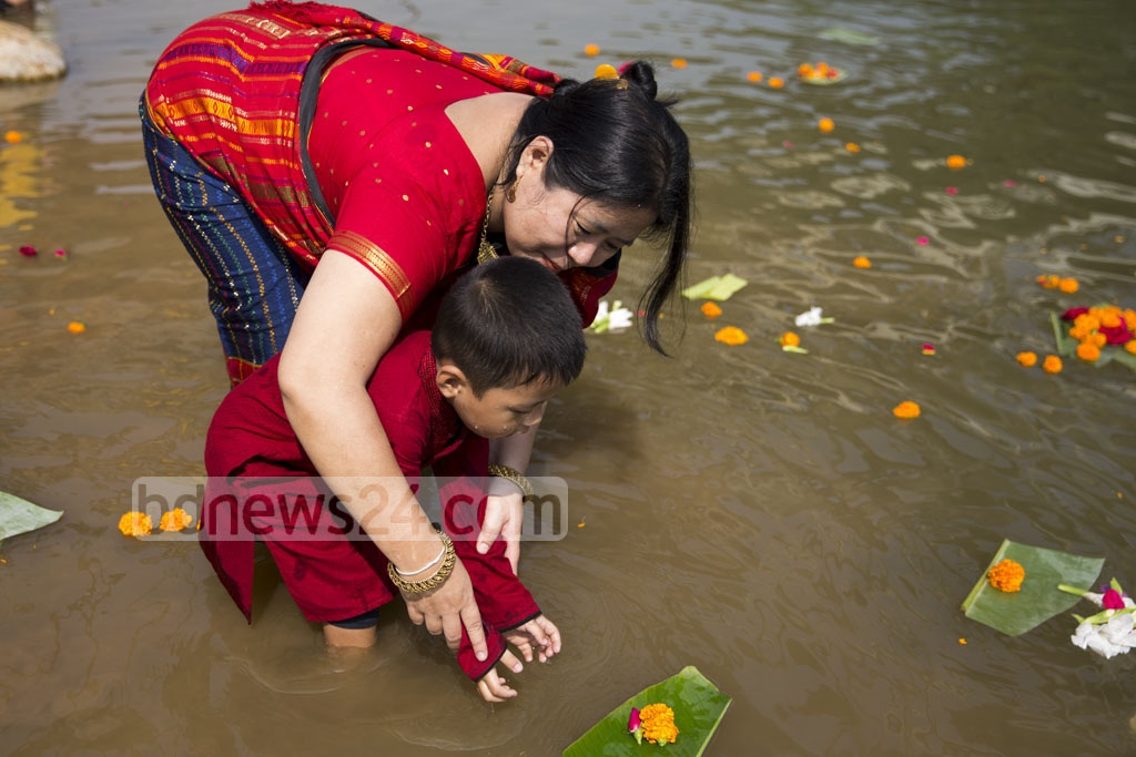 A Chakma woman and child release flowers at Dhaka's Crescent Lake on Thursday to celebrate Baishabi. Photo: Mostafigur Rahman