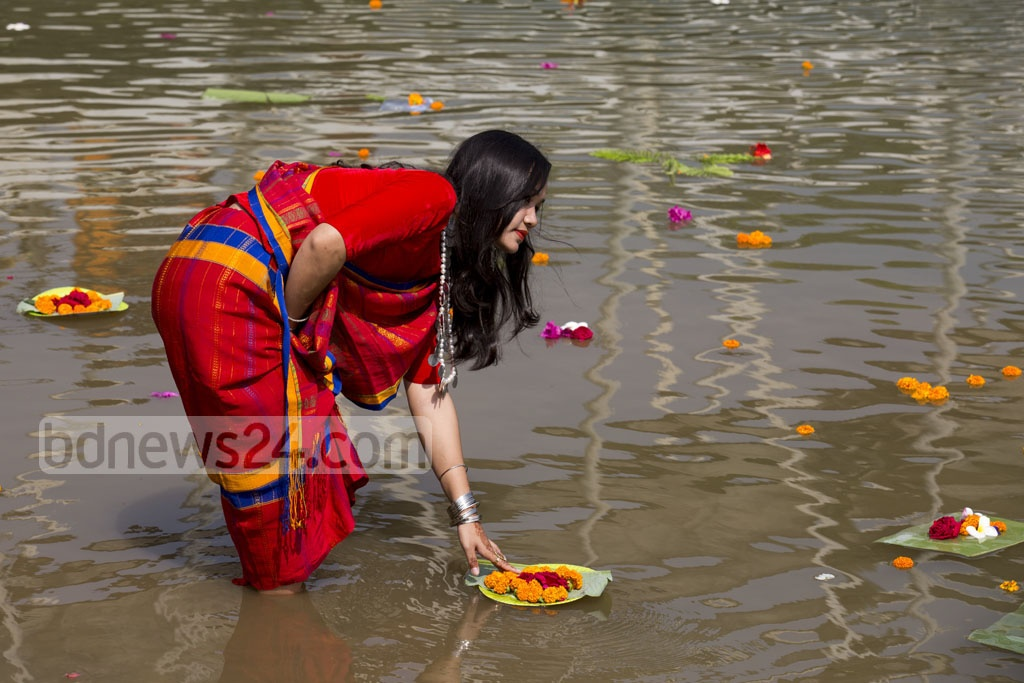A woman from a minority ethnic group releases flowers at Dhaka's Crescent Lake on Thursday to celebrate Baishabi. Photo: Mostafigur Rahman