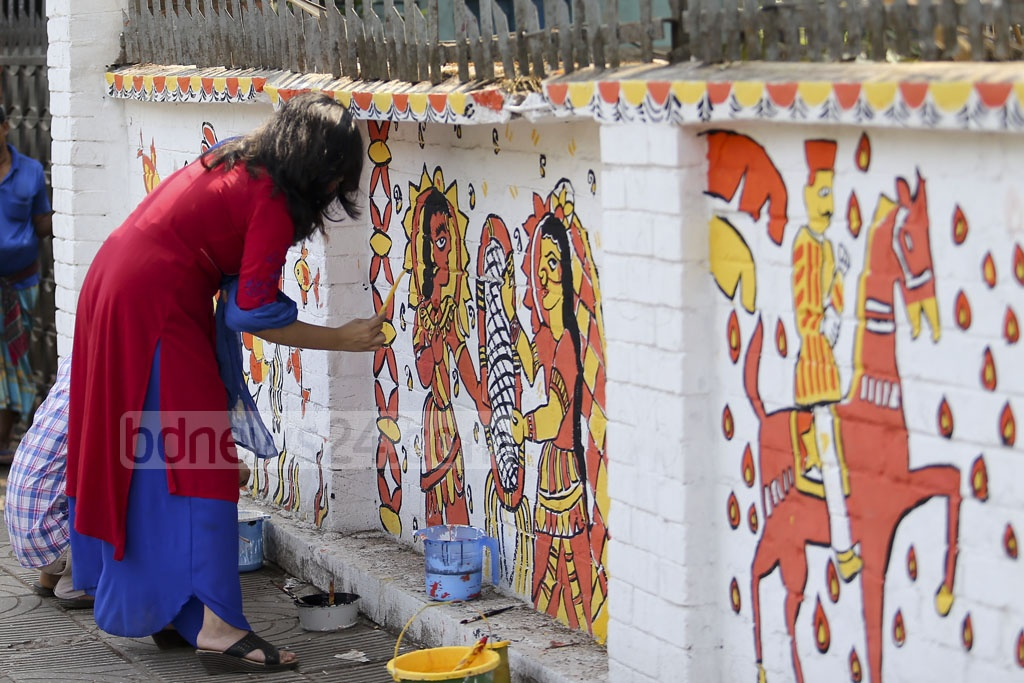 A student paints graffiti on the wall of Dhaka University's Faculty of Fine Arts on Friday as they prepare for Bangla New Year celebrations.