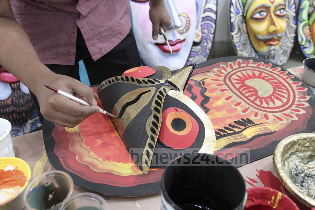 A student of Dhaka University's Faculty of Fine Arts paints a mask on Friday as they prepare for Bangla New Year celebrations.