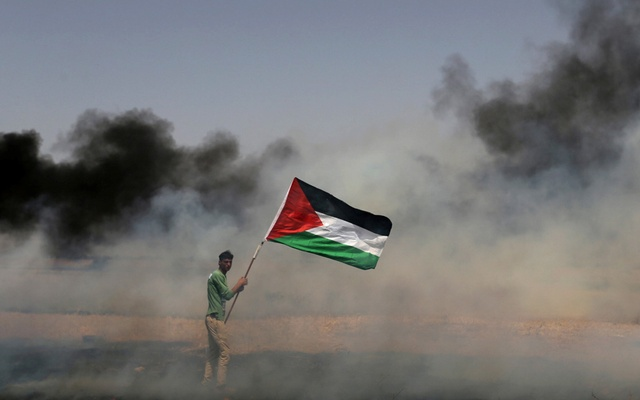 A demonstrator holds a Palestinian flag during clashes with Israeli troops at a protest where Palestinians demand the right to return to their homeland, at the Israel-Gaza border in the southern Gaza Strip, Apr 13, 2018. Reuters