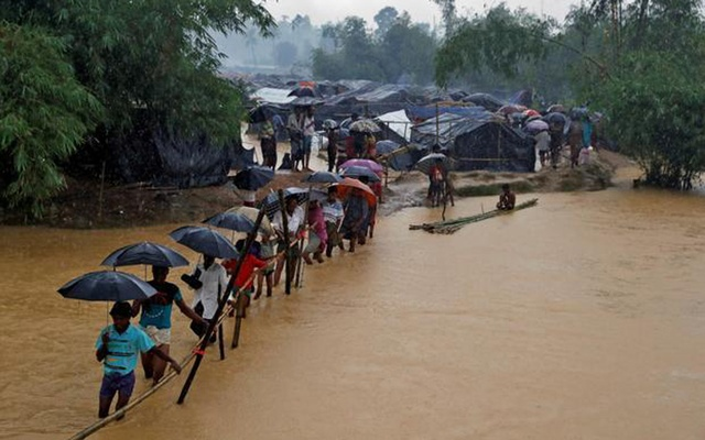 Rohingya refugees leave their makeshift shelters as they are flooded due to heavy rain, in Cox's Bazar, Bangladesh on Sept 19, 2017. Reuters