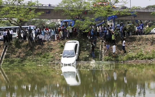 People gather near the Kuril flyover in Dhaka as firemen try to salvage an ill-fated car that plunged into water on Wednesday.