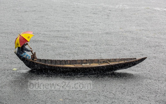 A boatman operates his craft on the Buriganga River, warding off the rain with an umbrella. Photo: Mostafigur Rahman