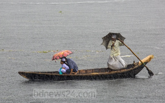A group crosses the Buriganga River on a boat lashed by rain near Dhaka's Waiz Ghat. Photo: Mostafigur Rahman