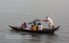 People returning home after a long day are suddenly caught in a shower on the Buriganga River. Photo: Mostafigur Rahman