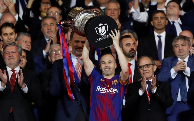 Barcelona's Andres Iniesta celebrates by lifting the trophy after the match as the King of Spain Felipe VI applauds the team's victory in the King's Cup on Apr 21, 2018. Reuters
