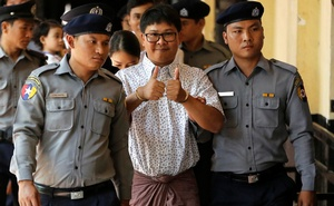 Detained Reuters journalist Wa Lone is escorted by police before a court hearing in Yangon, Myanmar Apr 20, 2018. Reuters
