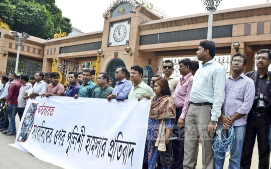 Journalists form a human chain to protest against police action on a reporter and a cameraman of Bangla TV in front of the DMP headquarters in Dhaka on Tuesday.