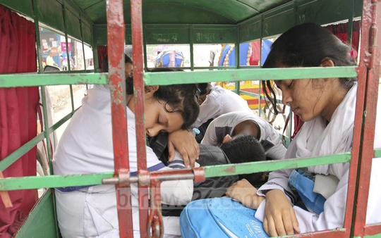 Exhausted school children could barely keep their eyes open in a van at Section 6 in the capital's Mirpur on Tuesday. Photo: asif mahmud ove.
