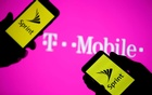 A smartphones with Sprint logo are seen in front of a screen projection of T-mobile logo, in this picture illustration taken Apr 30, 2018. Reuters