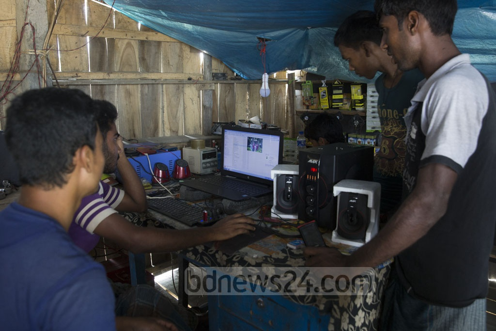 A group of young men download music onto their smartphones from the net over a computer at Gaburia Union's Khalishabunia Village in Satkhira's Shyamnagar. Though this area near the Sundarbans is not on the power grid, locals use solar energy to power the computer. Photo: Mostafigur Rahman