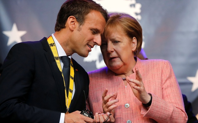 Macron talks to German Chancellor Angela Merkel after being awarded Charlemagne Prize in Aachen Germany