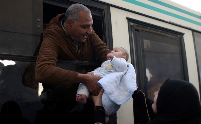 A man holds his grandson before he leaves in a bus to travel into Egypt through Rafah border crossing after it was opened by Egyptian authorities for humanitarian cases, in the southern Gaza Strip May 13, 2018. REUTER