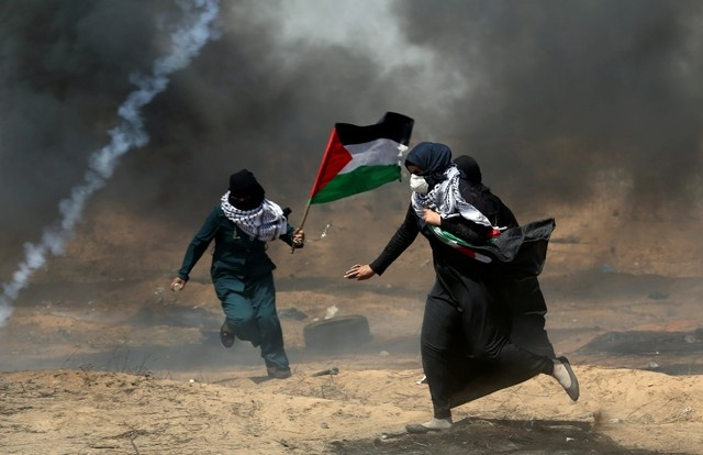 Female demonstrators run for cover from tear gas fired by Israeli forces during a protest where Palestinians demand the right to return to their homeland, at the Israel-Gaza border in the southern Gaza Strip, May 11, 2018. REUTERS