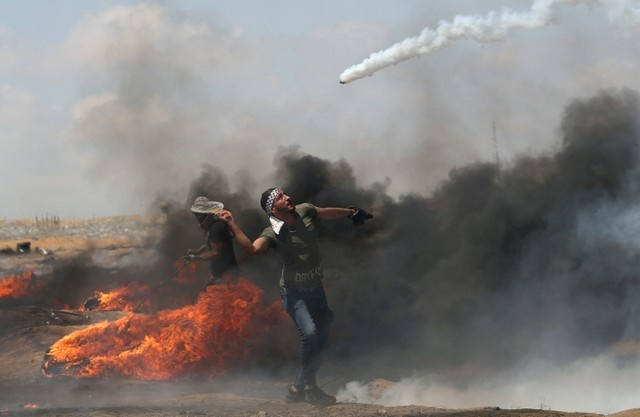 A demonstrator uses a racket to return a tear gas canister fired by Israeli troops during a protest where Palestinians demand the right to return to their homeland, at the Israel-Gaza border in the southern Gaza Strip, May 11, 2018. REUTERS