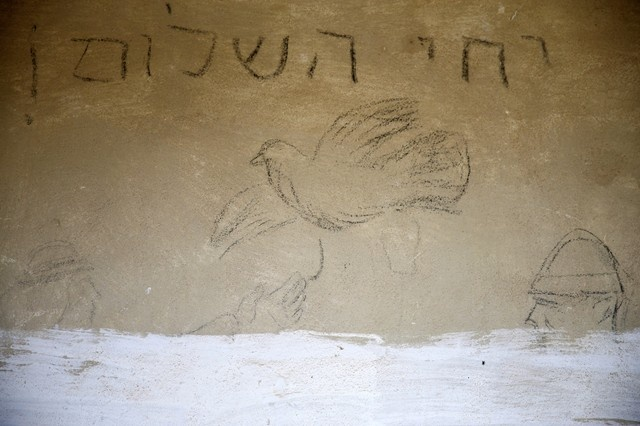 Graffiti writing is seen inside an old Arab building, which was part of the Palestinian village of Hiribiya, in Kibbutz Zikim, Israel May 11, 2018. Picture taken May 11, 2018. The writing in Hebrew reads,